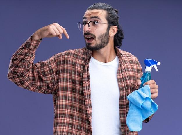 파란색 벽에 고립 된 자신에 걸레 포인트 스프레이 병을 들고 티셔츠를 입고 측면 젊은 잘 생긴 청소 사람을보고 놀란