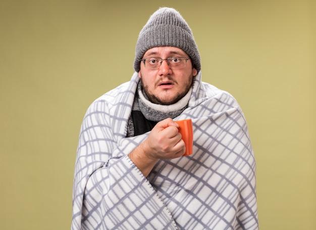Sorpreso dall'aspetto fotocamera maschio malato di mezza età che indossa cappello invernale e sciarpa avvolta in un plaid che tiene una tazza di tè