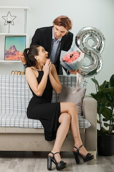 Sorpreso a guardarsi l'un l'altro giovane coppia durante la felice giornata delle donne ragazzo con bouquet in piedi dietro al divano con una ragazza nel soggiorno