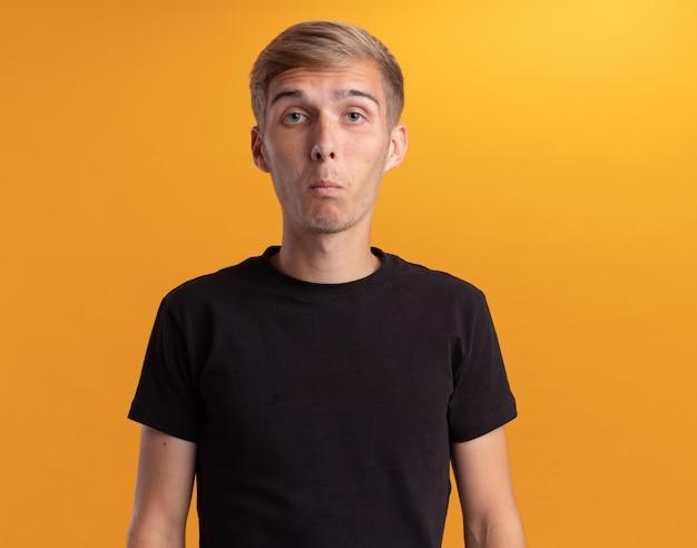 Sorpreso guardando davanti giovane bel ragazzo che indossa la camicia nera isolata sulla parete gialla