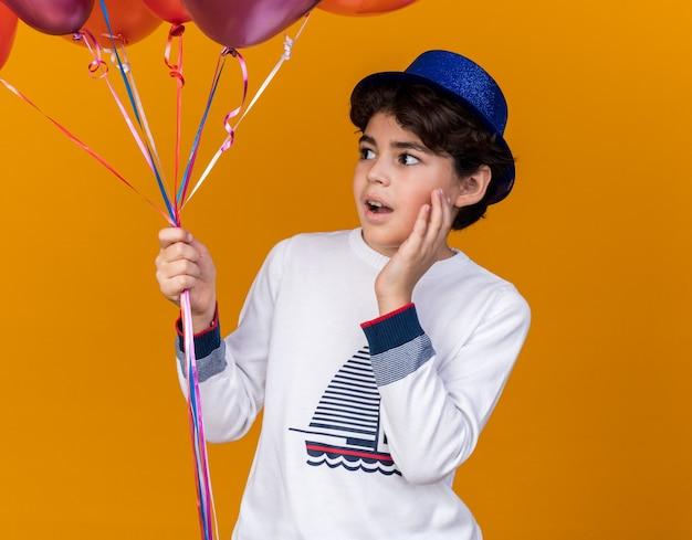 풍선을 들고 파란색 파티 모자를 쓰고 놀란 찾고 측면 어린 소년
