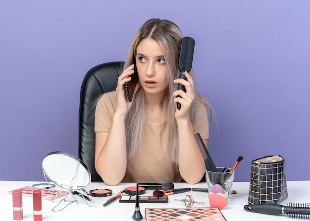 놀란 표정의 아름다운 소녀는 화장 도구를 들고 탁자에 앉아 파란 배경에 격리된 머리를 빗질하는 전화로 말한다