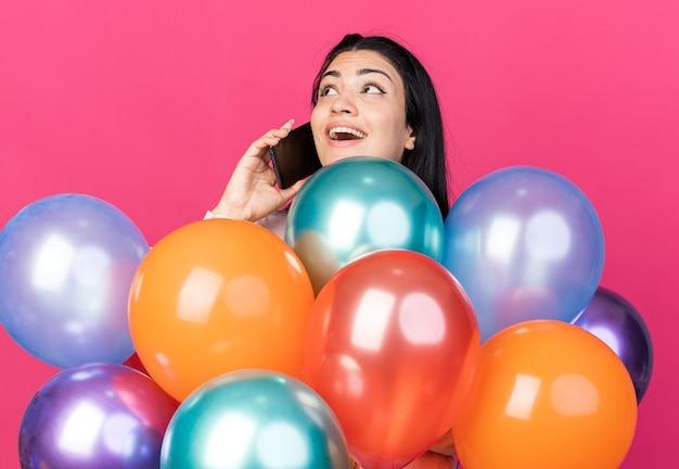 풍선 뒤에 서 있는 놀란 표정의 아름다운 소녀는 분홍색 벽에 격리된 전화로 말한다