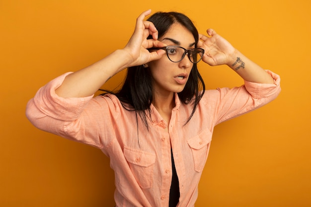 Sorpreso guardando lato giovane bella ragazza che indossa la maglietta rosa che indossa e che tiene i vetri isolati sulla parete gialla