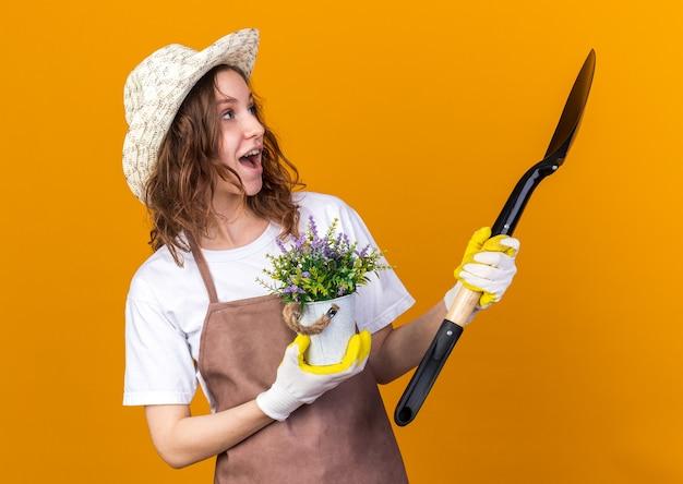 Sorpreso guardando lato giovane giardiniere femminile che indossa cappello da giardinaggio tenendo il fiore in vaso di fiori con vanga