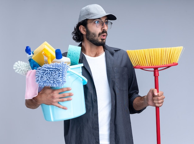 Surprised looking at side young handsome cleaning guy wearing t-shirt and cap holding bucket of cleaning tools with mop isolated on white wall