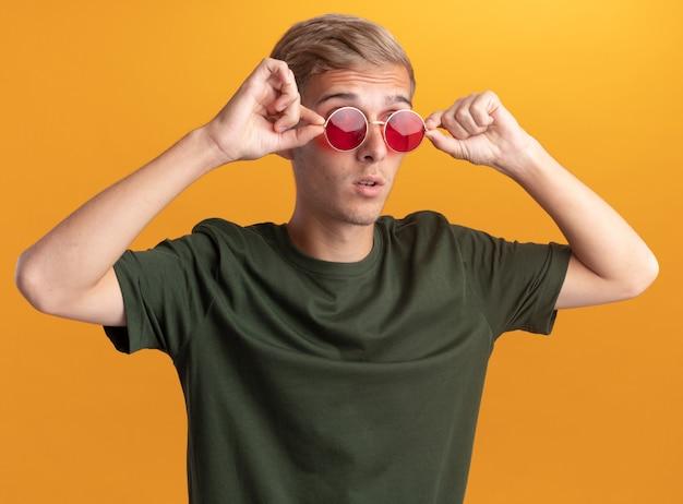 Sorpreso guardando al lato giovane bel ragazzo che indossa la camicia verde e occhiali isolati sulla parete gialla