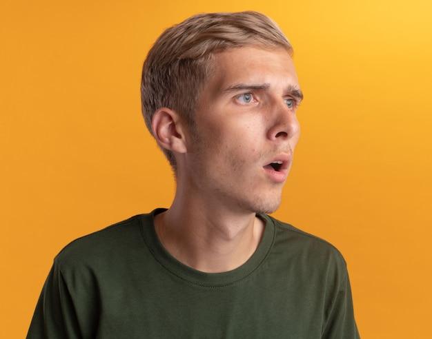 Sorpreso guardando lato giovane bel ragazzo che indossa la camicia verde isolato sul muro giallo