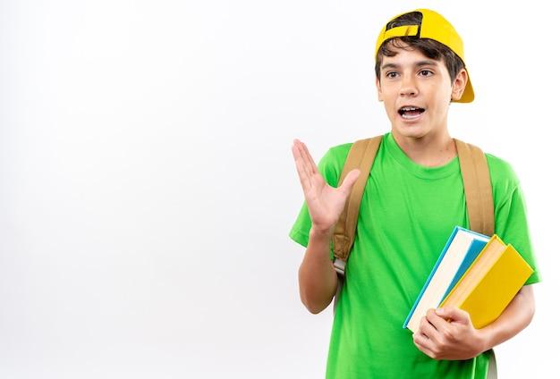 白い壁に隔離された本を保持しているキャップとバックパックを身に着けている驚きの側面の若い男子生徒