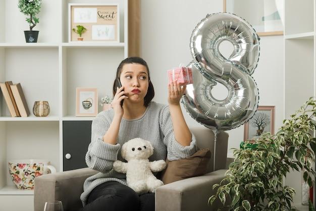 Sorpreso guardando bella ragazza il giorno delle donne felici tenendo presente parla al telefono seduto sulla poltrona in soggiorno