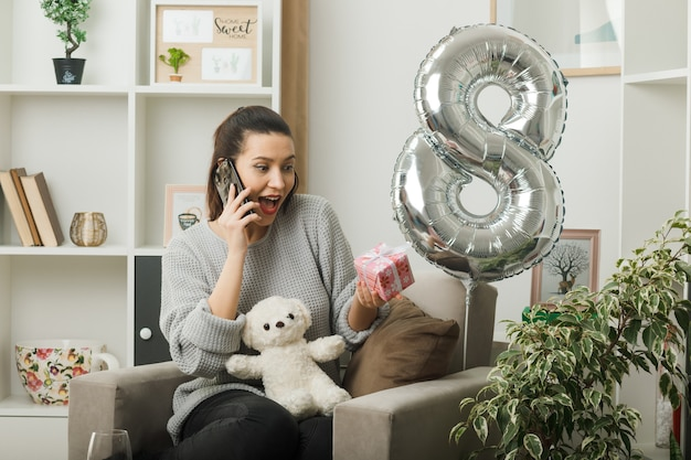 Удивленная девушка в день счастливой женщины, держащая в руках подарок, разговаривает по телефону, сидя на кресле в гостиной