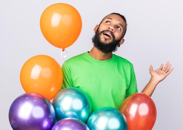 Удивленный глядя вверх молодой афро-американский парень в партийной шляпе, стоящий среди воздушных шаров, протягивая руку, изолированную на белой стене
