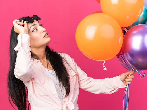Surprised looking up young beautiful girl wearing glasses holding balloons