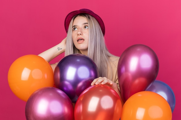 Surprised looking up young beautiful girl wearing party hat with dental braces standing behind balloons isolated on pink wall