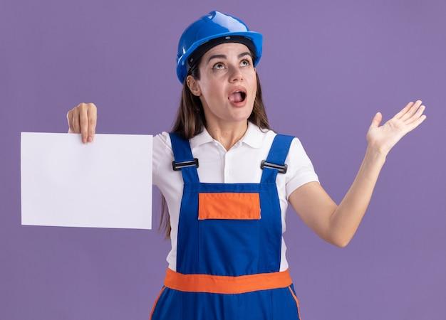Sorpreso guardando la giovane donna del costruttore in uniforme che tiene la mano di diffusione della carta isolata sulla parete viola