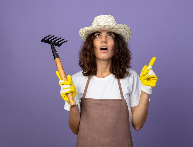 熊手ポイントを上に保持している園芸帽子と手袋を身に着けている制服を着た若い女性の庭師を見て驚いた