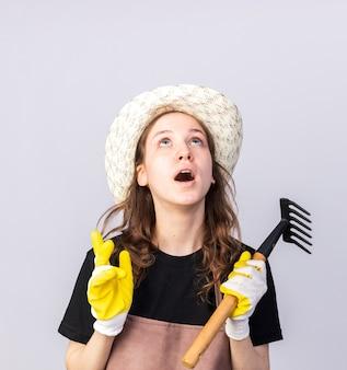 흰 벽에 격리된 갈퀴를 들고 장갑을 낀 원예용 모자를 쓴 젊은 정원사를 올려다보고 놀란다