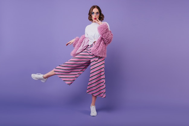 Surprised lovely girl in white shoes posing on purple wall during indoor photoshoot. full-length portrait of interested curly woman in pink pants and elegant fur jacket.