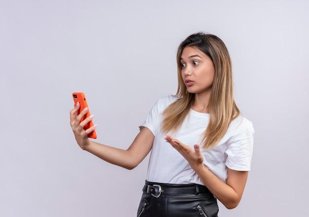 Una giovane donna adorabile sorpresa in maglietta bianca che solleva la mano mentre esamina il telefono cellulare su una parete bianca