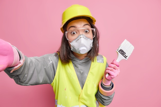 Surprised maintenance female worker wears uniform protective mask and glasses makes photo of herself holds paint brush uses building tools for repair