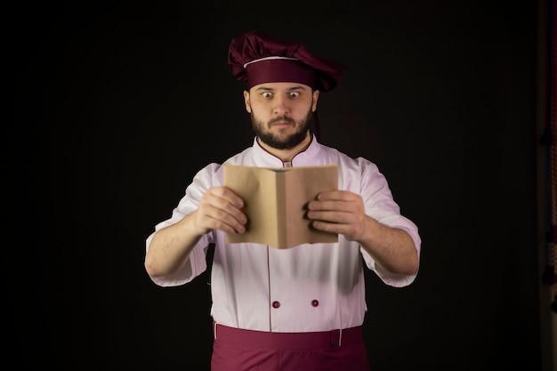 Удивленный повар-повар в фартуке смотрит на книгу рецептов на черном фоне