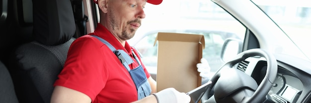 Surprised male courier taking digital tablet out of cardboard box