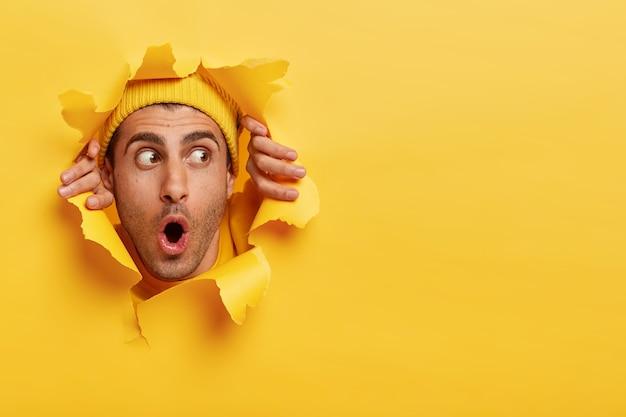 종이 구멍을 통해 놀란 된 남성 얼굴입니다. 감정적 인 놀란 젊은 남자가 노란색 모자를 쓰고