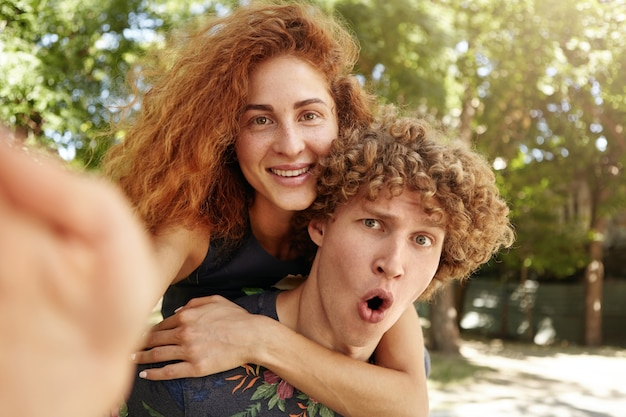 Surprised male giving piggyback ride to his red-haired girlfriend