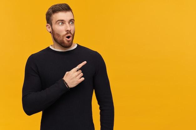 Удивленный мужчина, красивый парень с волосами брюнетки и бородой. имеет пирсинг. в черном свитере. шокирован и показывает пальцем вправо на пространство для копирования, изолированное над желтой стеной