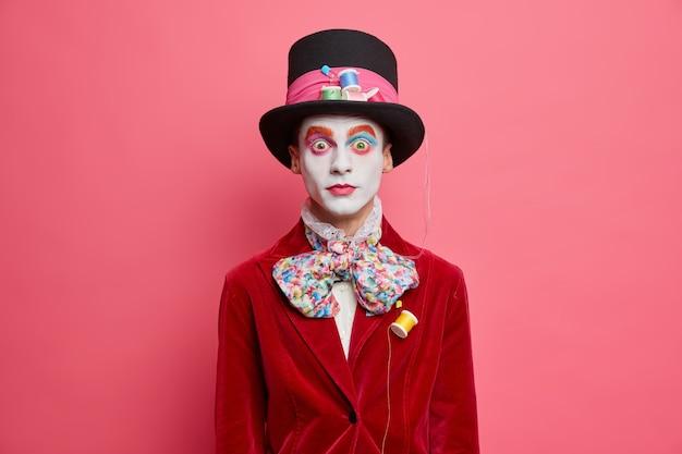 驚いた男性の帽子屋は帽子の蝶ネクタイを身に着け、ハロウィーンのカーニバルに存在する赤いベルベットのジャケットはバラ色の壁に対して屋内でカラフルな化粧スタンドを身に着けています