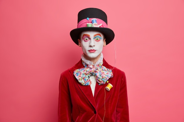Surprised male hatter wears hat bowtie and red velvet jacket being present on halloween carnival wears colorful makeup stands indoor against rosy wall