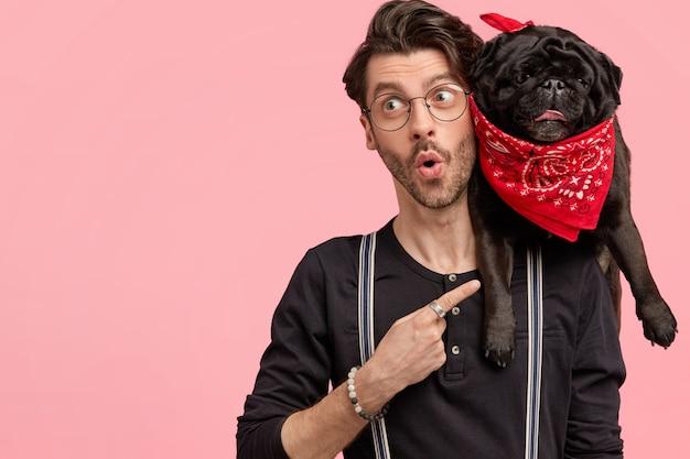 Hipster maschio sorpreso vestito con una camicia nera alla moda, indica il suo buffo cane con bandana rossa, si sente sorpreso di averlo comprato a basso prezzo, isolato su un muro rosa con uno spazio vuoto a sinistra