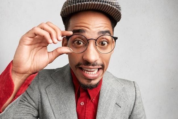 Nerd maschio sorpreso indossa occhiali rotondi, tiene la mano sul telaio, indossa berretto e giacca, sembra goffamente,