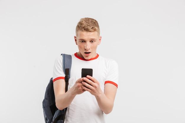 Удивленный ученик с чистой здоровой кожей, носящий рюкзак в чате на мобильном телефоне