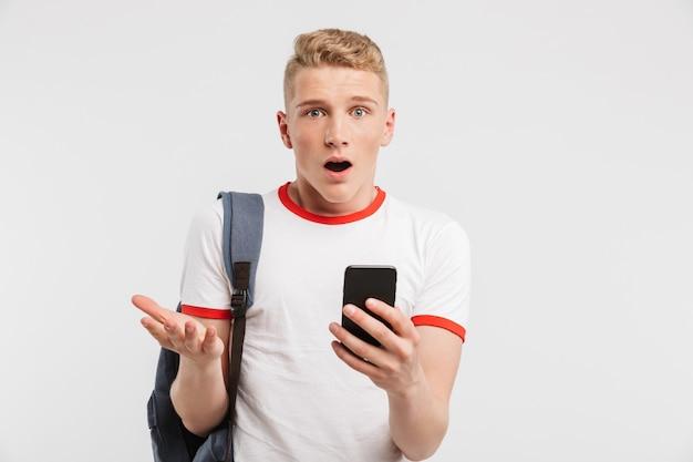 Удивленный мужчина студент с чистой здоровой кожей носить рюкзак с помощью мобильного телефона и выражая озадаченность, изолированные на белом