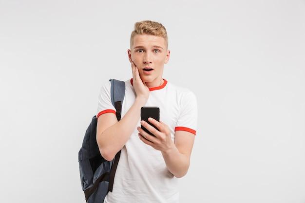 Удивленный мужчина студент с чистой здоровой кожей носить рюкзак с помощью мобильного телефона и касаясь щеки, изолированные на белом