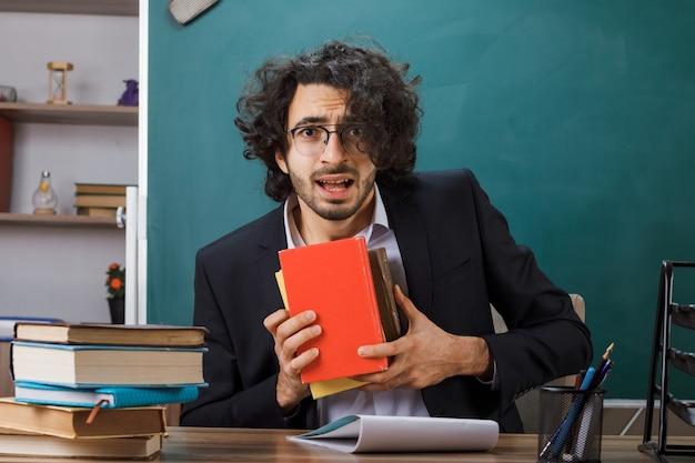 Insegnante maschio sorpreso con gli occhiali che tiene un libro seduto al tavolo con gli strumenti della scuola in classe