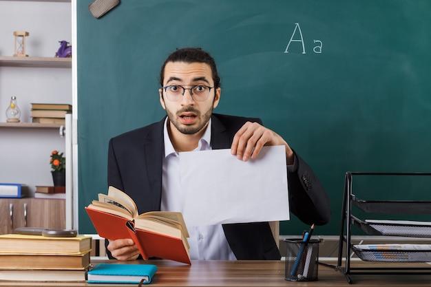 Insegnante maschio sorpreso con gli occhiali in possesso di carta con libro seduto al tavolo con strumenti scolastici in classe