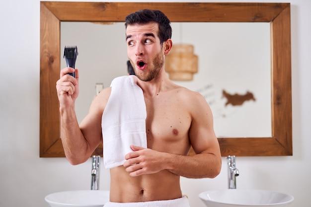 Удивленный мужчина с электробритвой в руке с полотенцем на плече стоит возле зеркала в ванне утром