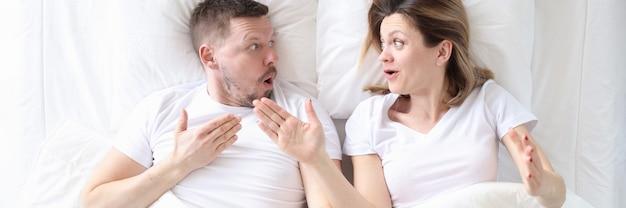 Удивленный мужчина и женщина обсуждают в постели концепцию семейной жизни