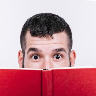 Surprised man behind book