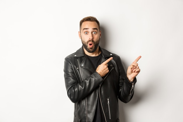 Surprised man in cool black leather jacket pointing fingers at upper right corner, showing logo or banner, white background.