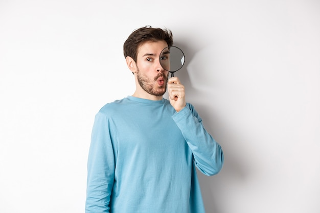 Surprised man found something, looking through magnifying glass with amazed face, standing over white background.