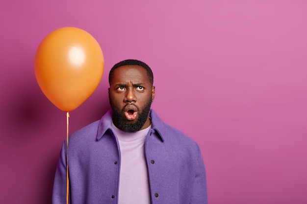 Surprised man frowns face, looks above with displeased shocked expression, thinks about something unpleasant, wears purple clothes, holds balloon