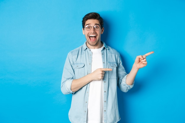 Surprised man in glasses pointing right at copy space, showing promo offer on blue background, standing over blue background