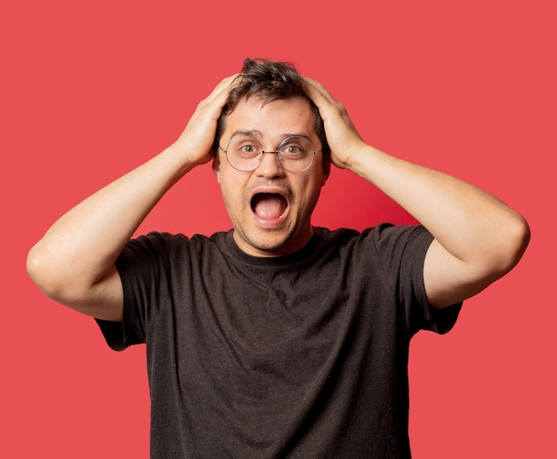 Surprised man in glasses and shirt on red space