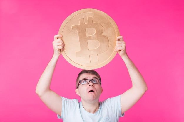 Удивленный мужчина держит большой золотой биткойн - популярная криптовалюта, виртуальные деньги