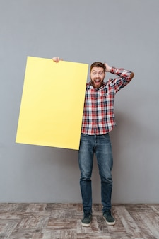 Surprised man holding blank board