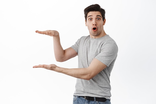Surprised man holding object, empty copy space between hands shaped in box, standing impressed against white wall