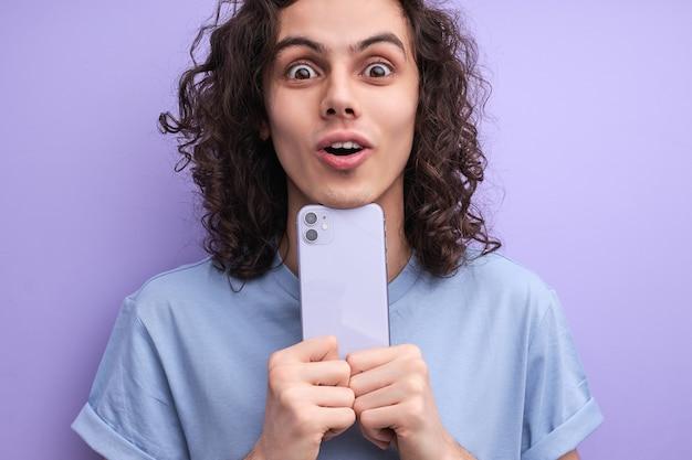 Удивленный мужчина держит телефон, читает невероятные новости в соцсети, в шоке. портрет мужчины в повседневной одежде, эмоционально реагирующего на новости или сообщение друга